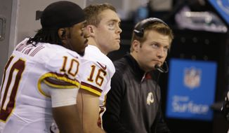 Washington Redskins quarterbacks Robert Griffin III, left,  and Colt McCoy on the bench during the first half of an NFL football game against the Indianapolis Colts Sunday, Nov. 30, 2014, in Indianapolis. (AP Photo/Darron Cummings)