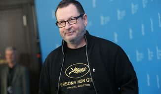 Director Lars von Trier reveals a tee shirt which has the Cannes film festival symbol and the slogan Persona Non Grata underneath as he poses for photographers at the photo call for the film Nymphomaniac at the International Film Festival Berlinale in Berlin, Sunday, Feb. 9, 2014. In 2011 Von Trier was asked to leave the Cannes film festival after a bizarre, rambling news conference in which he said he sympathizes with Adolf Hitler. (Photo by Joel Ryan/Invision/AP)