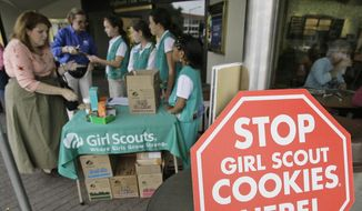 Girl Scouts from the Texas Council sell cookies,  Friday, Feb. 23, 2007, in Dallas. The Girl Scouts have marked their 90th year in the cookie business by getting most of the artificial fat out of all varieties of their iconic treats, which had been under attack by a few health-focused consumer groups. (AP Photo/Matt Slocum) ** FILE **