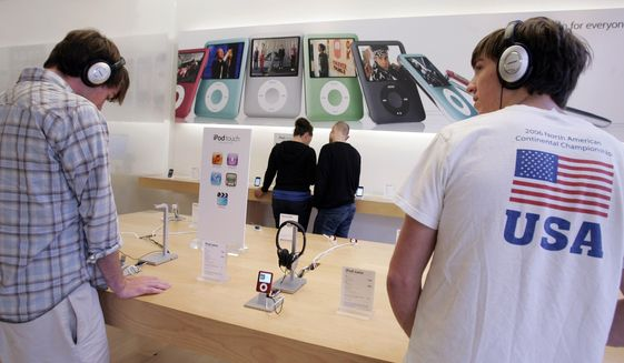 In this Oct. 19, 2007, file photo, customers try out the Apple iPod Nano at an Apple store in Palo Alto, Calif. (AP Photo/Paul Sakuma, File)