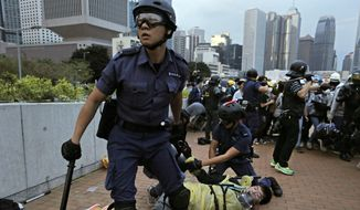 FILE - In this Monday, Dec. 1, 2014 file photo, a protester is arrested by police officers outside government headquarters in Hong Kong as pro-democracy protesters try to surround the headquarters, stepping up their movement for genuine democratic reforms after camping out on the city's streets for more than two months. An electoral pummeling for Taiwan's pro-Beijing ruling party and a new spike in pro-democracy protests in Hong Kong have delivered a reality check to Chinese President Xi Jinping just when he was riding a wave of high-profile diplomacy. (AP Photo/Vincent Yu, File)