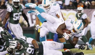 Miami Dolphins running back Lamar Miller (26) leaps over New York Jets defensive end Sheldon Richardson (91) for a touchdown during the fourth quarter of an NFL football game, Monday, Dec. 1, 2014, in East Rutherford, N.J. (AP Photo/Kathy Willens)