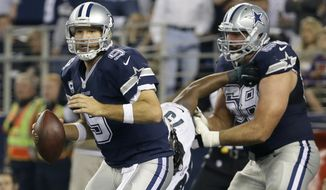 Dallas Cowboys quarterback Tony Romo (9) prepares to pass as Doug Free (68) helps against pressure from Philadelphia Eagles' Vinny Curry during an NFL football game, Thursday, Nov. 27, 2014, in Arlington, Texas. (AP Photo/Tony Gutierrez)