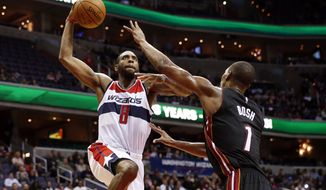 Washington Wizards forward Rasual Butler (8) prepares to dunk over Miami Heat center Chris Bosh (1) in the second half of an NBA basketball game, Monday, Dec. 1, 2014, in Washington. The Wizards won 107-86. (AP Photo/Alex Brandon)