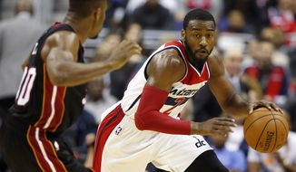 Washington Wizards guard John Wall (2) drives with the ball against Miami Heat guard Norris Cole (30) in the second half of an NBA basketball game, Monday, Dec. 1, 2014, in Washington. The Wizards won 107-86. (AP Photo/Alex Brandon)