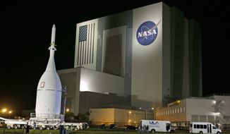 In this Nov. 11, 2014, file photo, the Orion Spacecraft moves by the Vehicle Assembly Building on its approximately 22-mile journey from the Launch Abort System Facility at the Kennedy Space Center to Space Launch Complex 37B at the Cape Canaveral Air Force Station in Cape Canaveral, Fla. The test flight for Orion is scheduled to launch on Dec. 4. (AP Photo/John Raoux, File)