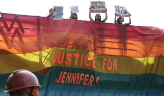 "Protesters hang a rainbow banner from the foot bridge near the U.S. Embassy to demand justice for the Oct. 11, 2014 killing of Filipino transgender Jennifer Laude at the former U.S. naval base of Subic northwest of Manila, Monday, Dec. 1, 2014. U.S. marine PFC Joseph Scott Pemberton was tagged as the suspect in the killing which the protesters termed as a ""hate crime"" against LGBT (Lesbians Gays Bisexual and Transgender) Filipinos. (AP Photo/Bullit Marquez)"