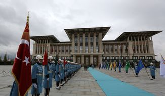 Military honour guard stand outside the main building of the new Presidential Palace complex after a welcome ceremony for Russian President Vladimir Putin in Ankara, Turkey, Monday, Dec. 1, 2014. Putin arrived in Turkey for a one-day visit and met with Erdogan at his huge new palace on once-protected farm land and forest in Ankara, becoming the second foreign dignitary after the Pope Francis to be hosted at the lavish, 1000-room complex.(AP Photo/Burhan Ozbilici)
