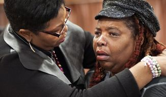 Dell Taylor, right, is comforted by the Rev. Traci Blackmon, a member of the Ferguson Commission appointed by Missouri Gov. Jay Nixon, during the opening meeting of the commission at the Ferguson Community Center in Ferguson, Mo. Monday, Dec. 1, 2014. The 16-person panel was chosen by Missouri's governor to help find long-term solutions after the Ferguson police shooting of an unarmed man. (AP Photo/Sid Hastings)