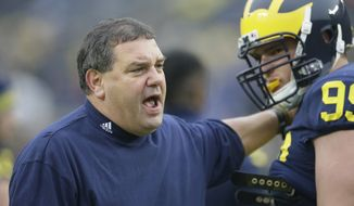 Michigan head coach Brady Hoke talks with defensive tackle Matthew Godin during warmups before the NCAA college football game against Maryland in Ann Arbor, Mich., Saturday, Nov. 22, 2014. (AP Photo/Carlos Osorio)