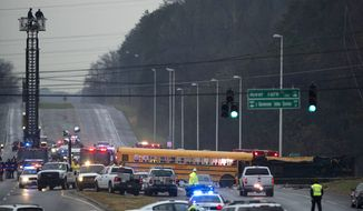 Emergency personnel close off the scene where two school buses serving Chilhowee Intermediate School and Sunnyview Primary School crashed in Knoxville, Tenn., Tuesday, Dec. 2, 2014. At least three people died in the accident. (AP Photo/Knoxville News Sentinel, Paul Efird)
