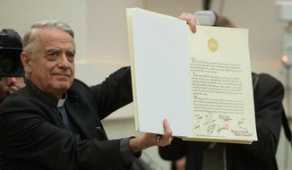 Vatican spokesman Federico Lombardi shows the joint Declaration of Religious Leaders against Modern Slavery, signed Tuesday by religious leaders from a half-dozen faiths. (AP Photo/L'Osservatore Romano)