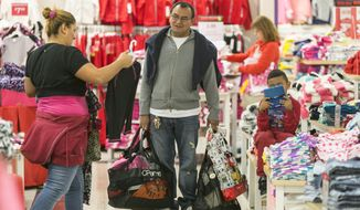 In this Nov. 28, 2014 file photo, shoppers Manuel Orellano, center, with his daughter Marcela, left, and her son Manuel, 6, shop for children's clothing at JCPenney at the Glendale Galleria shopping mall in Glendale, Calif.   (AP Photo/Damian Dovarganes, File) **FILE**