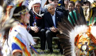 President Barack Obama and Chairman of the Standing Rock Sioux Tribe David Archambault II, left, watch dancers during a visit to the Standing Rock Indian Reservation in Cannon Ball, N.D. on June 4, 2014. Mr. Obama on Wednesday, Dec. 3, 2014 announced an initiative to improve conditions and opportunities for American Indian youth, more than one-third of whom live in poverty. (AP Photo/Charles Rex Arbogast, File)