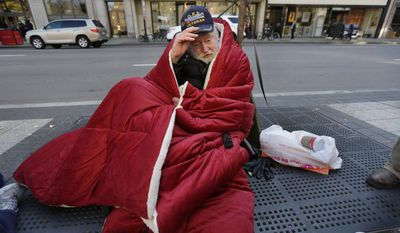 Homeless Korean War veteran Thomas Moore, 79, adjusts his hat while wrapped in a blanket on a sidewalk in Boston on Nov. 20, 2013. Moore, who said he accidentally killed his best friend with a phosphorous grenade during one firefight and spent months afterward at Walter Reed Army Medical Center in Washington, also said he has no interest in getting a government-subsidized apartment. (Associated Press) **FILE**