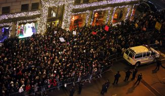 A group of protesters with signs, rear, rally against the decision not to indict the police officer involved in the death of Eric Garner as they mix with spectators near Rockefeller Center during a ceremony to light the Rockefeller Center Christmas Tree, Wednesday, Dec. 3, 2014, in New York. (AP Photo/Jason DeCrow)