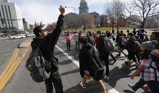 East High School students march in a protest against the Ferguson, Missouri grand jury decision, along a busy street in front of the state Capitol in Denver, Wednesday Dec. 3, 2014. Authorities said four Denver police officers were hit by a car while watching the high school students protest.   (AP Photo/Brennan Linsley)