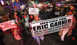 Illuminated by red police siren lights, people march on Broad St. in Newark, N.J. to protest police brutality and the previous day's decision to not indict the New York City police officer involved in the death of Eric Garner in Staten Island on Thursday, Dec. 4, 2014. (AP Photo/The Record of Bergen County - Northjersey.com, Kevin R. Wexler)