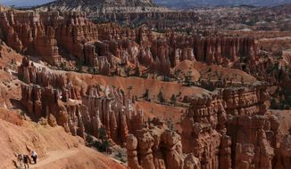 Hikers make their way to Sunset Point from Thors Hammer Sunday, Sept., 6, 2009, in Bryce Canyon National Park, Utah.  Both Zion and Bryce were formed millions of years ago when the Earth's crust violently heaved, leaving behind stunning, unique arrays of rock formations.   (AP Photo/Ross D. Franklin)