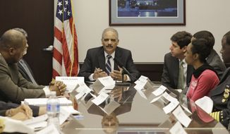 U.S. Attorney General Eric Holder, center, holds a roundtable meeting with law enforcement, local officials, and community leaders Thursday, Dec. 4, 2014, in Cleveland. The US Justice Department issued a report Thursday that says Cleveland police officers use excessive and unnecessary force far too often, are poorly trained in tactics and firearm use and place the public and their fellow officers in danger because of reckless behaviors. (AP Photo/Tony Dejak)