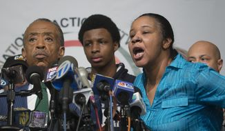 Esaw Garner, right, wife of Eric Garner, responds to a question during a news conference at the National Action Network headquarters in New York on Wednesday, Dec. 3, 2014, after a grand jury's decision not to indict a New York police officer involved in her husband's death. At left is the Rev. Al Sharpton. (AP Photo/John Minchillo)