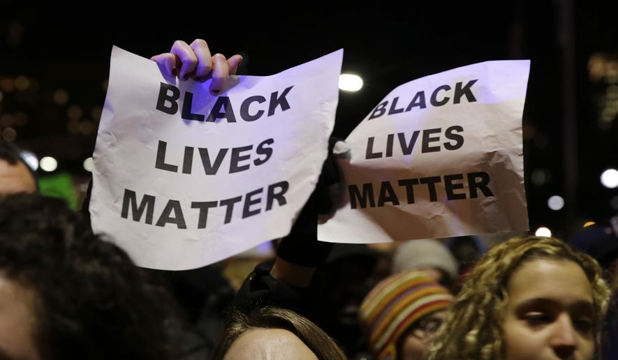 """In this Dec. 4, 2014 file photo, protestors in Boston hold up signs while chanting """"Black Lives Matter"""" during a demonstration against the deaths of two unarmed black men at the hands of white police officers in New York City and Ferguson, Mo. (AP Photo/Charles Krupa, file) ** FILE **"""