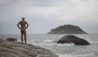 Pedro Ribeiro looks out at the sea from  Abrico beach, recently designated as nudist after a 20-year-battle, in Rio de Janeiro, Brazil, Thursday, Dec. 4, 2014. The law passed last month frees nudists from any threat of legal action and provides increased protection, including patrols to keep peeping Toms away. (AP Photo/Felipe Dana)