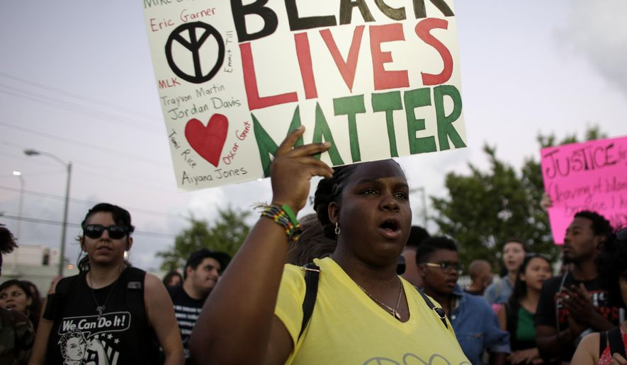 """Desiree Griffiths, 31, of Miami, holds up a sign saying """"Black Lives Matter"""", with the names of Michael Brown and Eric Garner, two black men recently killed by police, during a protest Friday, Dec. 5, 2014, in Miami. People are protesting nationwide against recent decisions not to prosecute white police officers involved in the killing of black men. (AP Photo/Lynne Sladky)"""