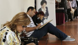 Job seekers fill out job applications at a job fair in Miami Lakes, Fla.  (AP)