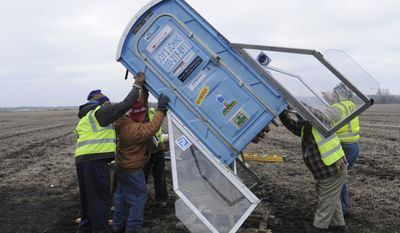 Members of the Michiana Rocketry prep a 10-foot, 450 pound porta-potty, mounted on rocket motors for launching, Saturday, Dec. 6, 2014, from a field in Three Oaks, Mich.(AP Photo/The Herald-Palladium, Don Campbell)