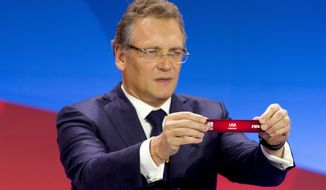 FIFA Secretary General Jerome Valcke displays tag with the name USA during the FIFA Women's World Cup draw in Gatineau, Quebec,. (AP Photo/The Canadian Press, Fred Chartrand)