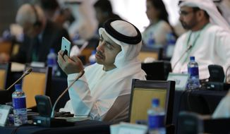 United Arab Emirates Foreign Minister Sheik Abdullah bin Zayed bin Sultan Al Nahyan checks his phone during the 10th International Institute for the Strategic Studies in Manama, Bahrain, Saturday, Dec. 6, 2014. (AP Photo/Hasan Jamali)