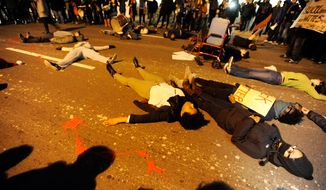 "Protestors stage a ""die-in"" in downtown Durham, N.C., on Dec. 5, 2014, during a demonstration against the non-indictments of the police officers involved in the deaths of Michael Brown in Ferguson, Missouri, and Eric Garner in New York City. (Associated Press/The Herald-Sun, Christine T. Nguyen) **FILE**"