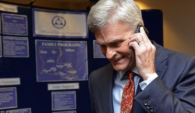 Louisiana Senatorial Candidate, Bill Cassidy, takes a call while going to meet supporters at his election watch party in Baton Rouge, La., Saturday, Dec. 6, 2014. (AP Photo/Bill Feig)
