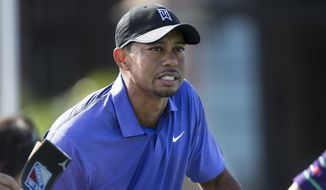 Tiger Woods holds himself up on the first tee during the third round of the Hero World Challenge golf tournament on Saturday, Dec. 6, 2014, in Windermere, Fla. Woods lost his voice overnight and was nauseated before and during the third round at Isleworth. (AP Photo/Willie J. Allen Jr.)
