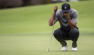 Tiger Woods covers his face as he waits to putt on the fifth green during the second round of the Hero World Challenge golf tournament on Friday, Dec. 5, 2014, in Windermere, Fla. (AP Photo/Willie J. Allen Jr.)