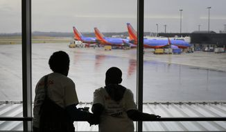 Malkia Wageed, left, looks at airplanes with her son, Tylee Lynn, 12, at Baltimore-Washington International Thurgood Marshall Airport, Saturday, Dec. 6, 2014, in Linthicum, Md., while they participate in Wings for Autism, an airport rehearsal for children with autism spectrum disorders, their families and aviation officials. (AP Photo/Patrick Semansky) ** FILE **