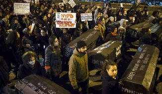 In this Dec. 4, 2014, file photo, protesters carry signs criticizing the police, and replicas of coffins during a march over the Brooklyn Bridge to protest a grand jury's decision not to indict the police officer involved in the death of Eric Garner, in New York. (AP Photo/John Minchillo, File)