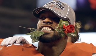 Ohio State cornerback Doran Grant holds a rose in his teeth after the Buckeyes 59-0 victory over Wisconsin in the Big Ten Conference championship NCAA college football game after midnight Sunday, Dec. 7, 2014, in Indianapolis. Ohio State won 59-0. (AP Photo/Darron Cummings)