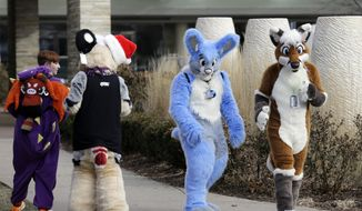 Frederic Cesbron, right and Maxim Durand, walk on the street outside the Hyatt Regency O'Hare hotel on Sunday, Dec. 7, 2014, in Rosemont, Ill. Thousands of people were evacuated after a chlorine gas leak at the hotel hosting the 2014 Midwest FurFest convention, where attendees dress as animals to celebrate art, literature and performance, in suburban Rosemont early Sunday morning. Investigators believe the leak at the hotel in Rosemont was caused intentionally and are treating it as a criminal matter. (AP Photo/Nam Y. Huh)