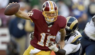 Washington Redskins quarterback Colt McCoy (16) is stacked by St. Louis Rams defensive end William Hayes (95) during the second half of an NFL football game in Landover, Md., Sunday, Dec. 7, 2014. The Rams defeated the Redskins 24-0. (AP Photo/Nick Wass)