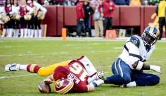 Washington Redskins quarterback Colt McCoy (16) is tossed to the ground on a sack by St. Louis Rams defensive end William Hayes (95) in the fourth quarter as the Washington Redskins play the St. Louis Rams in NFL football at FedExField, Landover, Md., Sunday, December 7, 2014. (Andrew Harnik/The Washington Times)