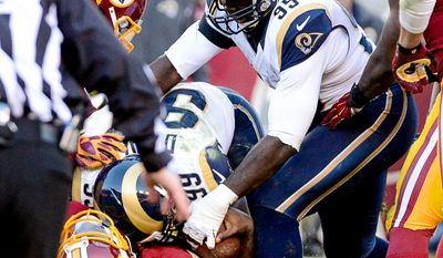 Washington Redskins quarterback Robert Griffin III (10) is sacked by St. Louis Rams defensive tackle Aaron Donald (99) after coming in as quarterback in the final two minutes of the game as the Washington Redskins play the St. Louis Rams in NFL football at FedExField, Landover, Md., Sunday, December 7, 2014. (Andrew Harnik/The Washington Times)