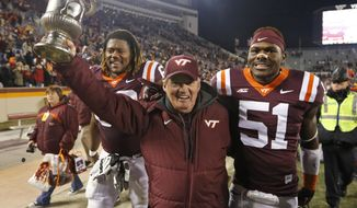 Virginia Tech head coach Frank Beamer celebrates beating Virginia with Virginia Tech linebacker Melvin Keihn (51) after an NCAA college football game in Blacksburg, Va., Saturday, Nov. 29, 2014. Virginia Tech won the game 24-20. (AP Photo/Steve Helber)
