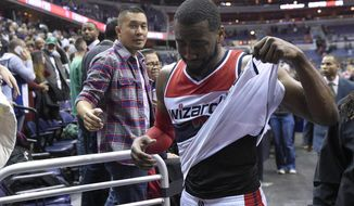 Washington Wizards guard John Wall (2) reacts after an NBA basketball game against the Boston Celtics, Monday, Dec. 8, 2014, in Washington. The Wizards won 133-132 in double overtime. (AP Photo/Nick Wass)