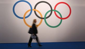 A woman walks in front of a board showing Olympics rings at the 127th International Olympic Committee session in Monaco, Monday, Dec. 8, 2014. (AP Photo/Lionel Cironneau)