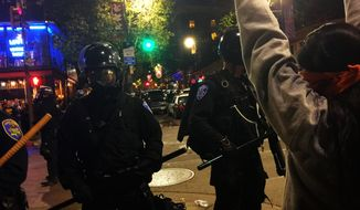 In this early Sunday, Dec. 7, 2014 photo provided by Gabriel Reyes, a protester stands in front of police, in Berkeley, Calif., as protesters angered by police killings in Missouri and New York demonstrated in the streets. (AP Photo/Gabriel Reyes)