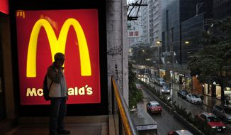 A man talks on a mobile phone next to a downtown McDonald's in Hong Kong in this April 2, 2014, file photo. (AP Photo/Vincent Yu, File)