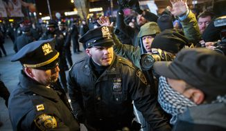 Police hold a barricade against protestors as media moves in during a demonstration outside the Barclays Center against a grand jury's decision not to indict the police officer involved in the death of Eric Garner, Monday, Dec. 8, 2014, in the Brooklyn borough of New York. Britain's Prince William, the Duke of Cambridge, and Kate, Duchess of Cambridge, not pictured, attended a NBA basketball game between the Cleveland Cavaliers and the Brooklyn Nets at Barclays Center. (AP Photo/John Minchillo)