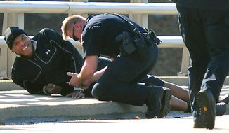 A Charlotte-Mecklenburg police officer tends to Carolina Panthers NFL football quarterback Cam Newton following a two-vehicle crash not far from the team's stadium in Charlotte, N.C., Tuesday, Dec. 9, 2014. (AP Photo/The Charlotte Observer, Todd Sumlin) MAGS OUT; TV OUT; NEWSPAPER INTERNET ONLY